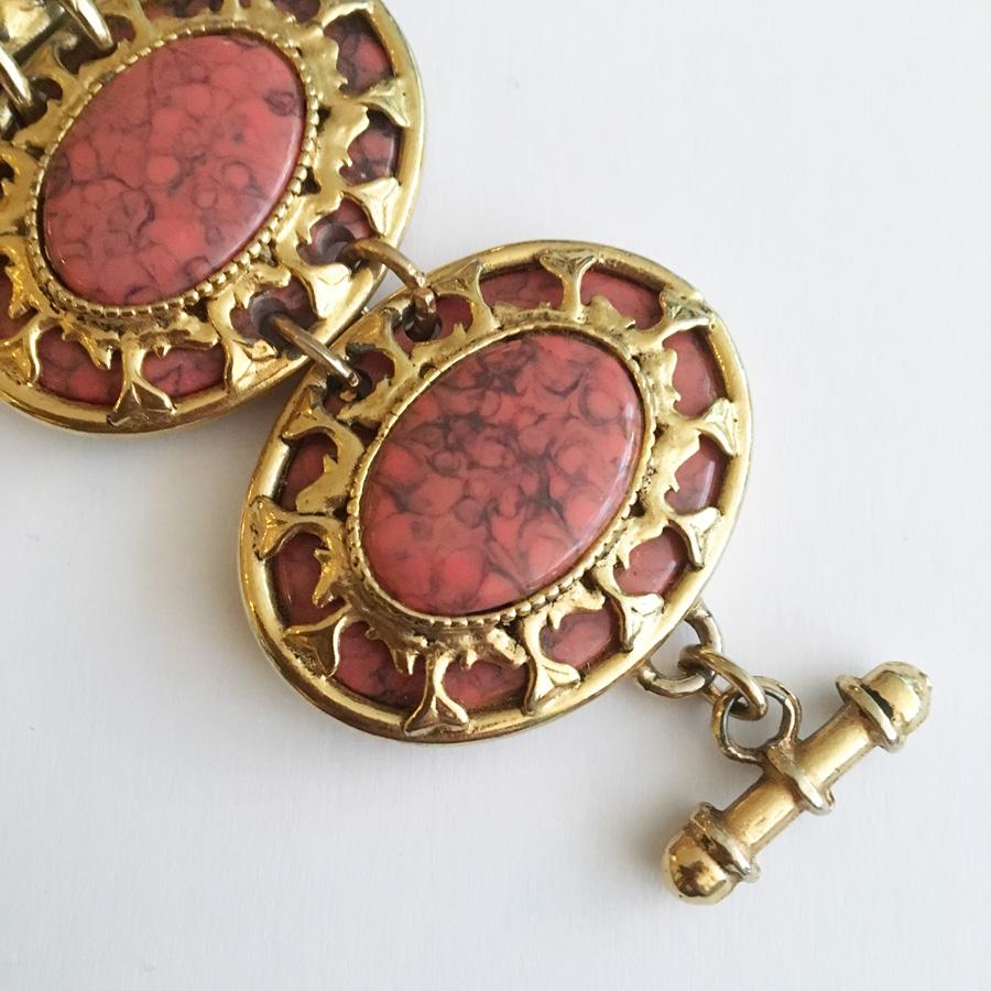 Anslående armband i gulmetall och marmorisering.