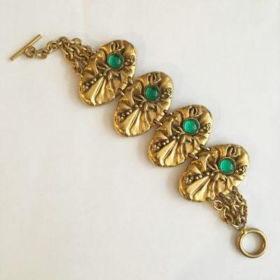 Armband, gulmetall och gröna stenar.