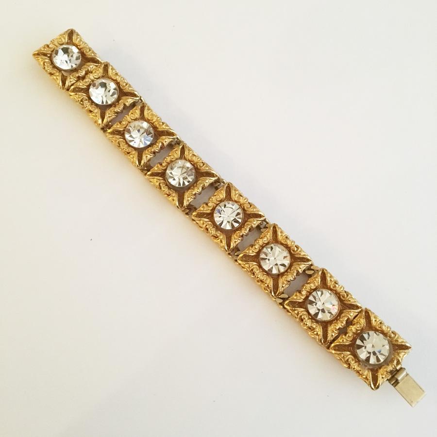 Armband i gulmetall med stiliserade bladverk och vita glasstenar. Vintage.