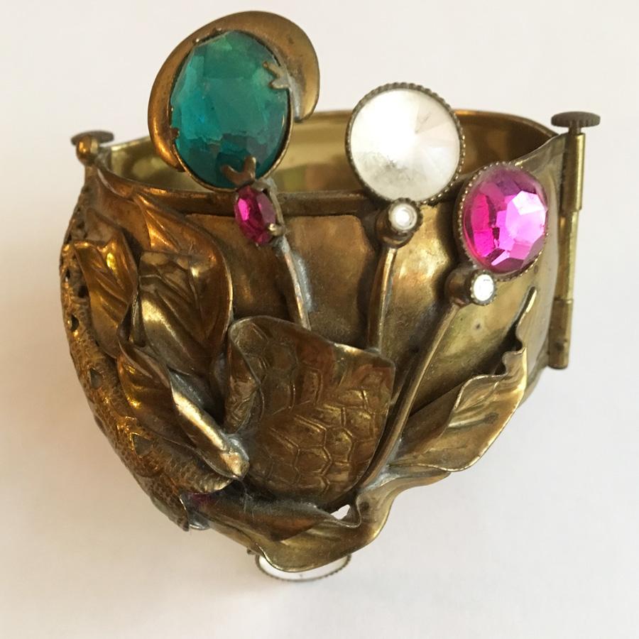 Bredare armband i mässing, med gröna, vita och rosa glasstenar. Från 1970-talet.