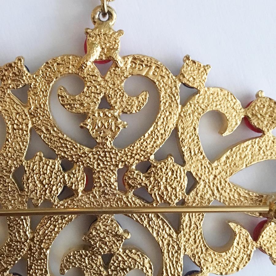 Brosch i gulmetall, med vit emalj och glasstenar.