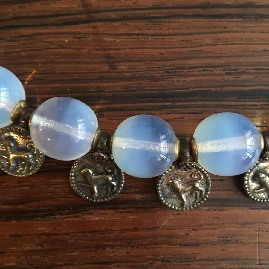 Halsbandet har medaljonger med hundar på. Glaspärlorna är vackert dimmiga.