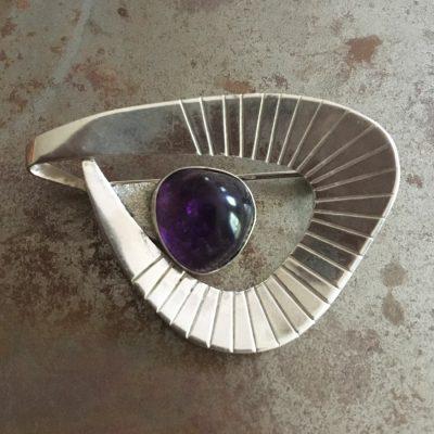 Tidstypisk brosch i silver och med dekorativ ametist.